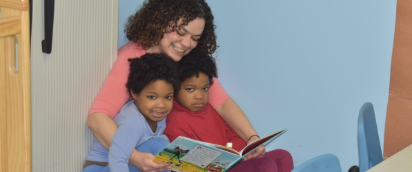Teacher reading a book to two children sitting in her lap